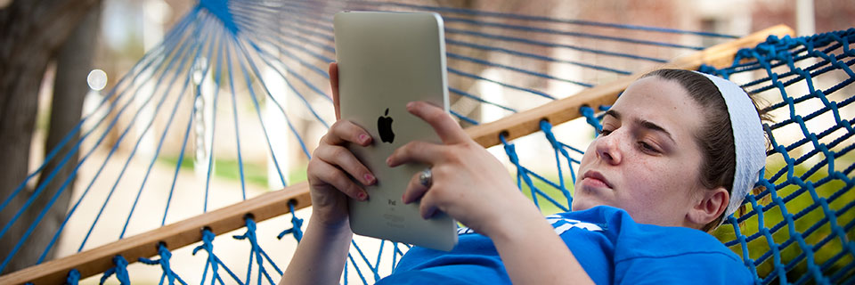 Student in hammock with an iPad