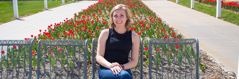 Annika Svoboda sits in front of some tulips on campus