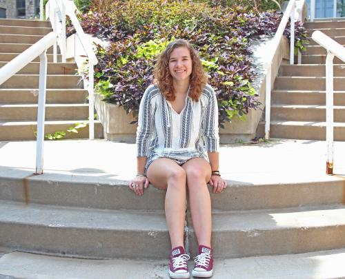 Emma Busch sits on steps on campus