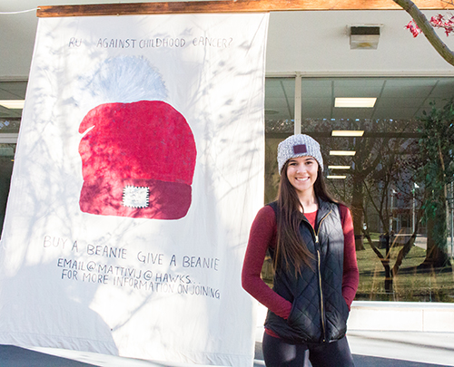 Julia Mattivi stands in front of a Love Your Melon banner.
