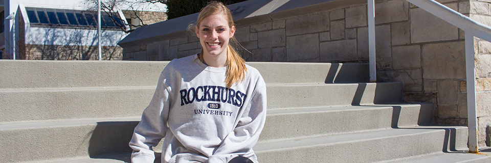 Karli Reichert sits on the steps by the bell tower