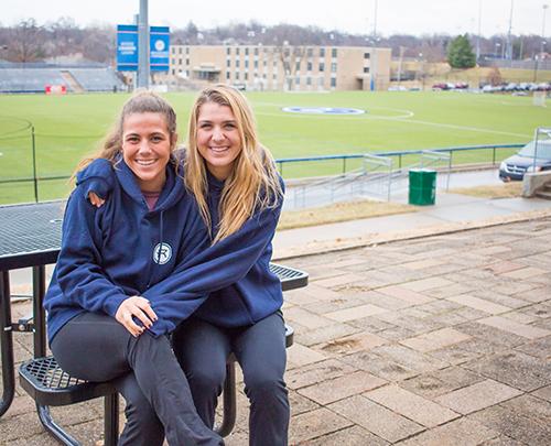 Angela and Lauren Merlo sit near the Rockhurst soccer field.