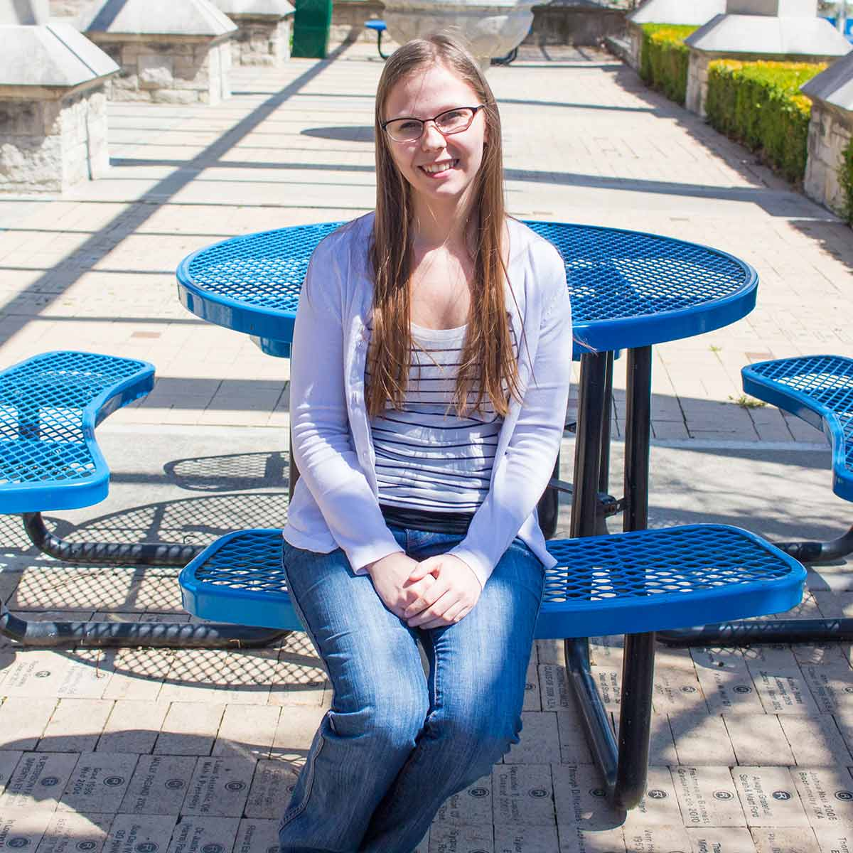 Alexandra Meyer sits at a table under the pergola.