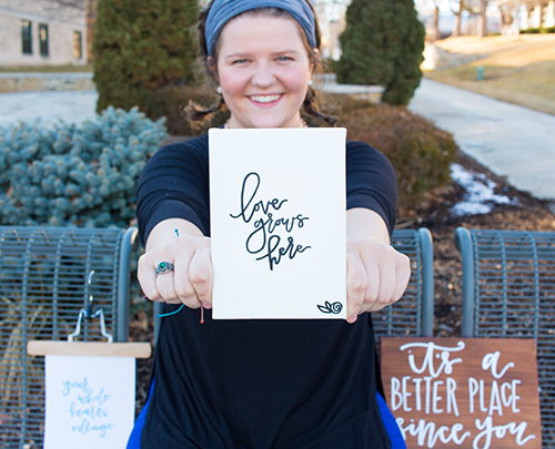 """Sarah Hummel holds a canvas with the words """"love grows here"""""""
