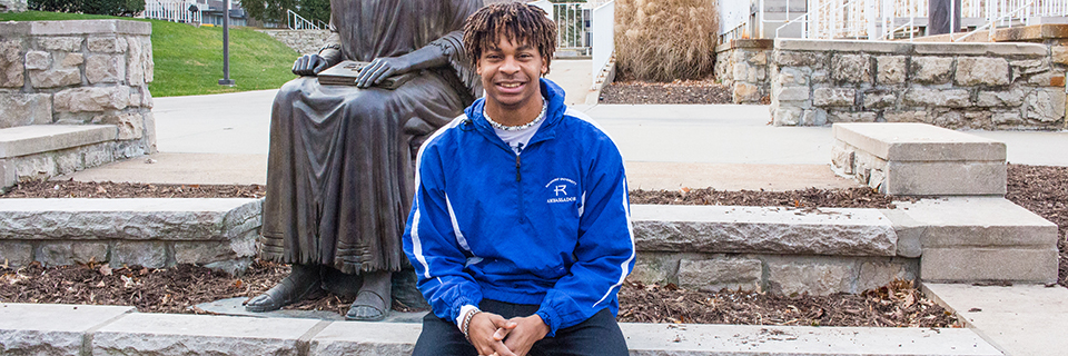 Shawn Taylor sits in front of the St. Ignatius statue
