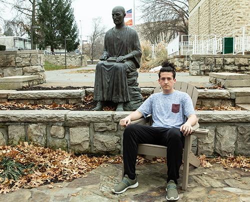 Stephen Wingo sits near the St. Ignatius statue