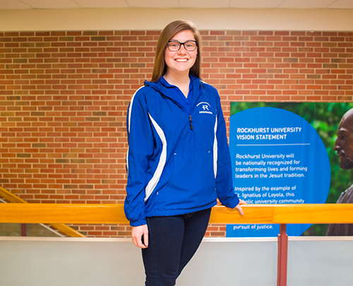 Sydney Hunter stands in front of a stairwell in Massman hall.