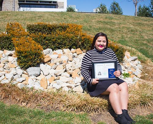 "Virginia Vanegas sits in front of the Rockhurst ""R"" shrub"