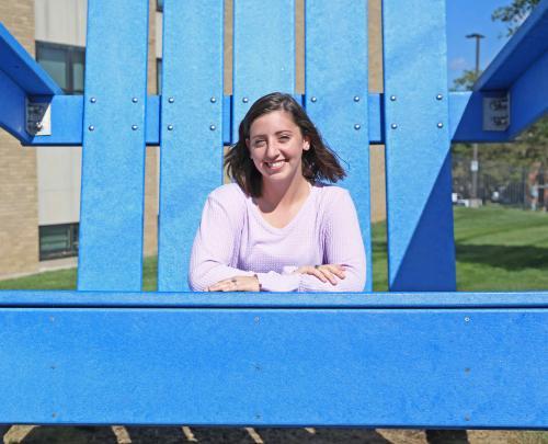 Caroline Adams sits in the big blue Adirondack chair on campus.