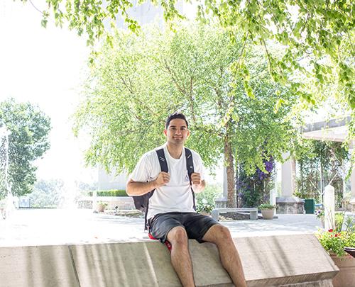 Cesar Aldana sits near the fountains on Rockhurst's campus