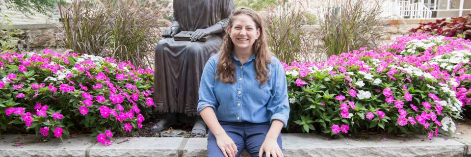 Claire Webster sits near the St. Ignatius statue