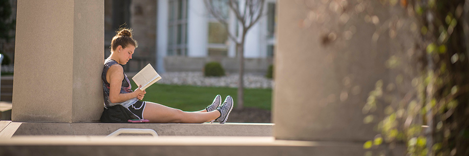 Student reads on ledge near pergola.