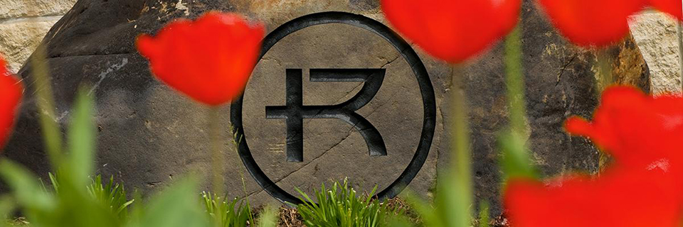 RU Circle Logo on Stone with Red Tulips