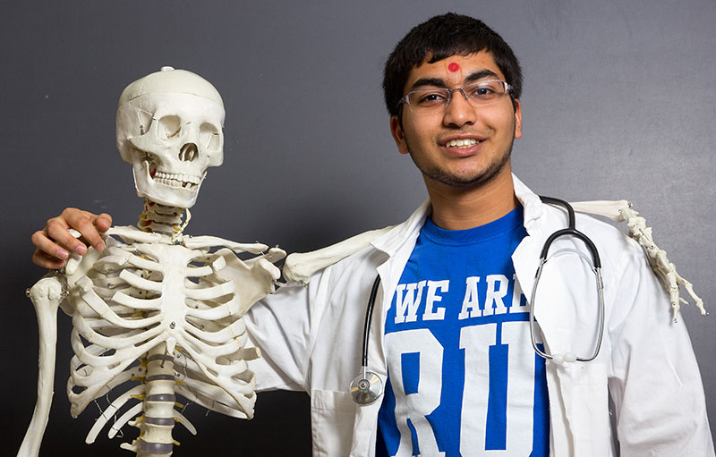 Pre-Med student posing with skeleton