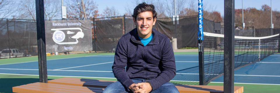 Nico Leon sits on a bench on the tennis courts.