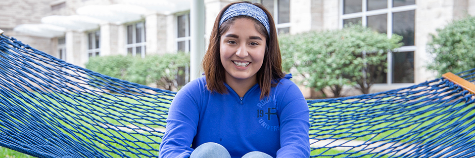 Paola Rodriguez sits on a hammock on campus.