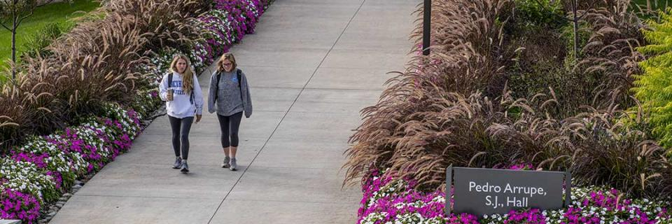 Students walking outside of Arrupe Hall.