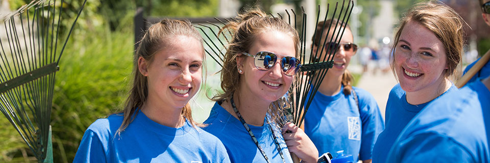Students with rakes on campus