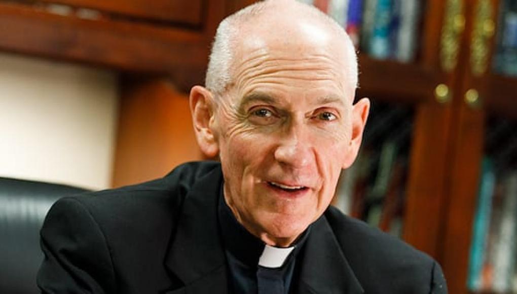 Fr. Curran sitting at his desk