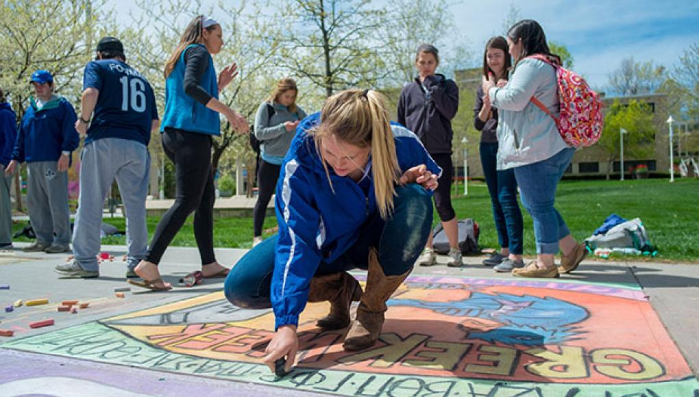Greek organization creating chalk drawings on the sidewalks of RU.