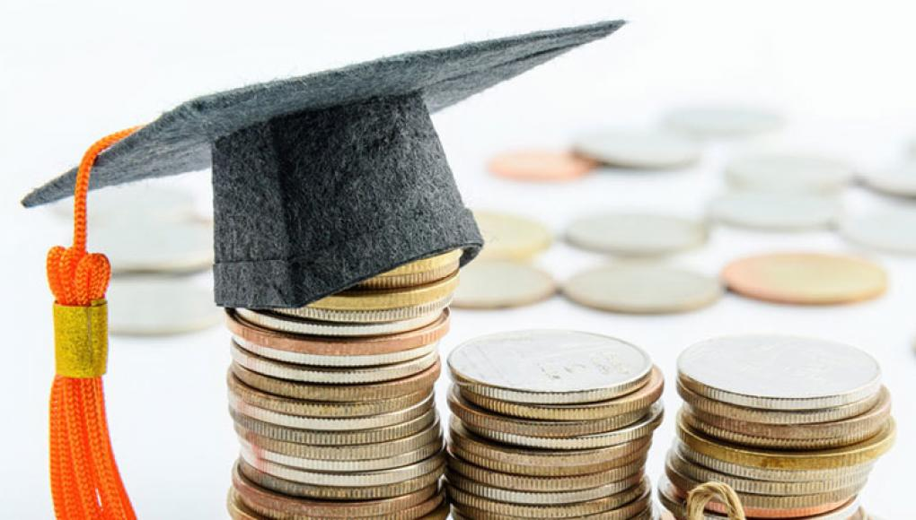 coins stacked with a graduation cap
