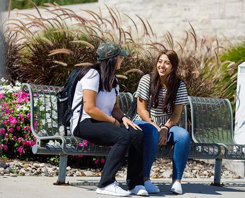 Students sitting on a bench and laughing
