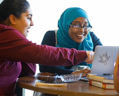 Students pointing at computer and smiling