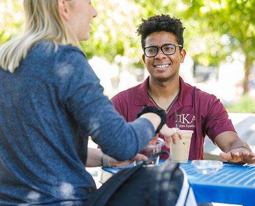 Students having a conversation while drinking coffee