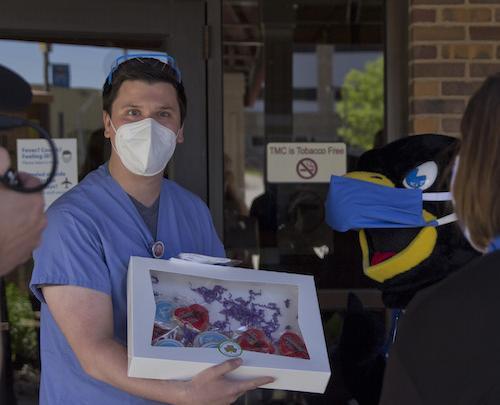 A nurse receiving treats from Rock E. Hawk