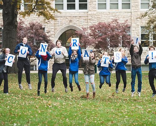 "Students jumping while holding letters that spell ""CONGRATS"""