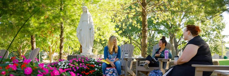 Three students in front of the Mary statue on campus