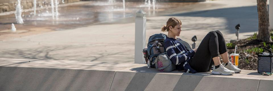 Student reads near bell tower on campus.