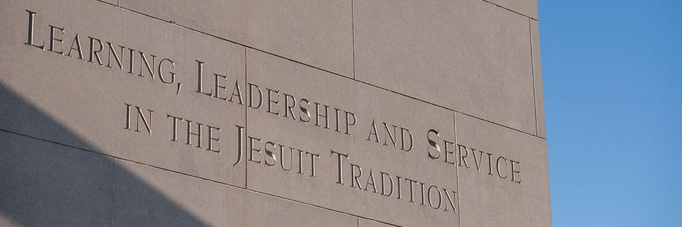 Bell tower inscription. Learning, leadership, and service in the Jesuit tradition