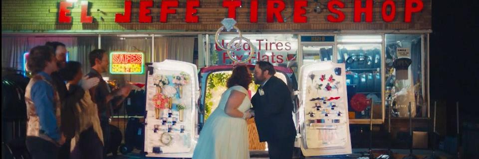 A married couple kissing in front of a storefront