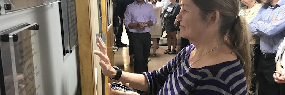 Woman blesses the door of a pantry with oil