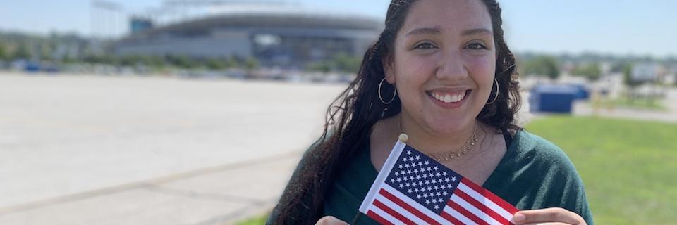 Student Karen Bravo holding an American flag