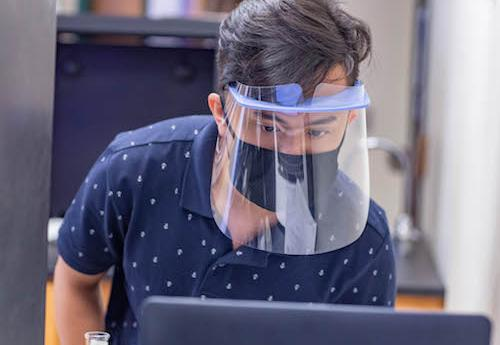 Student studying with personal protective equipment on