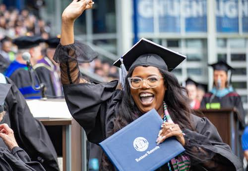 A graduate celebrating at commencement
