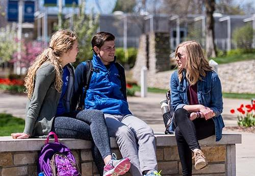 Students sitting on a bench outside