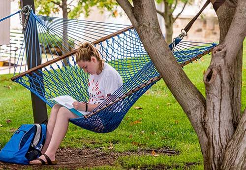 Student reads on a hammock