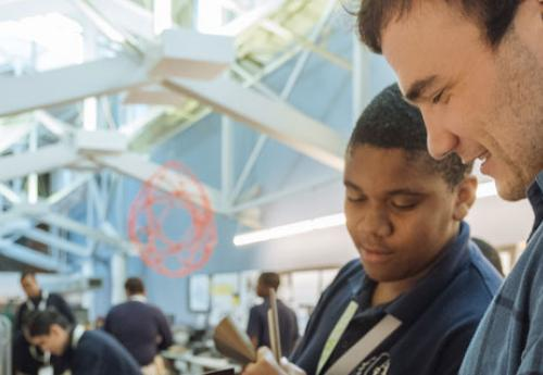 A Secondary Education student works with a high schooler at STEAM Studio KC
