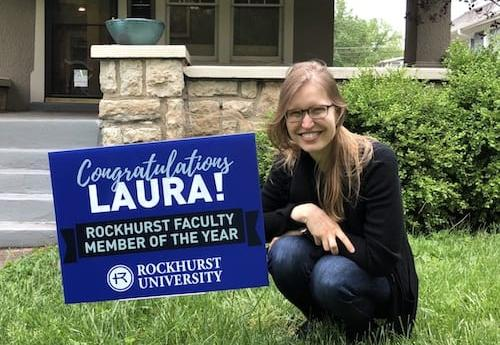 A faculty member next to a sign honoring her service