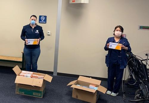 Hospital employees accepting protective equipment donations from a RU employee