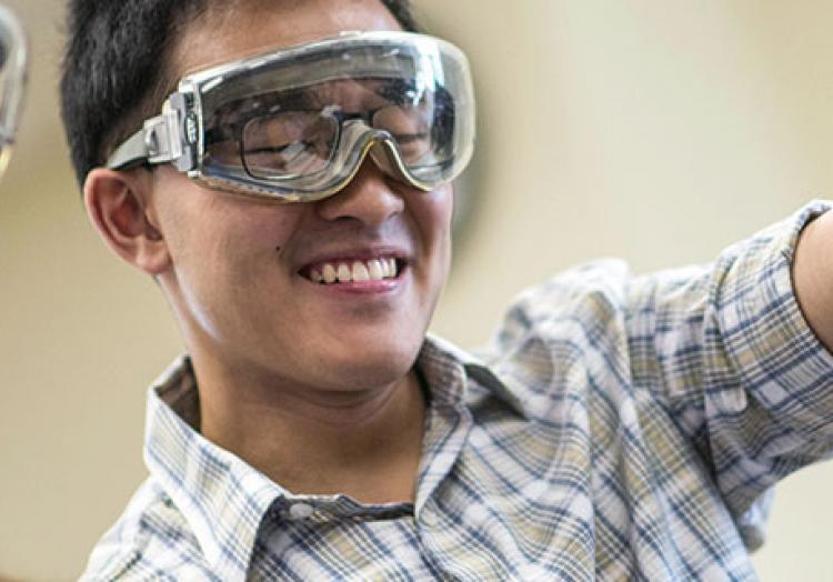 Student measuring liquid into a beaker