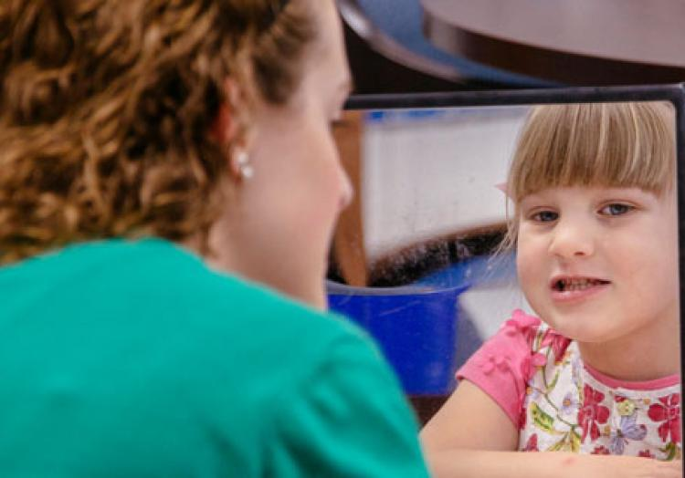 A communication sciences and disorders student works with a child at a clinic