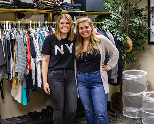 Two students stand in front of clothing rack